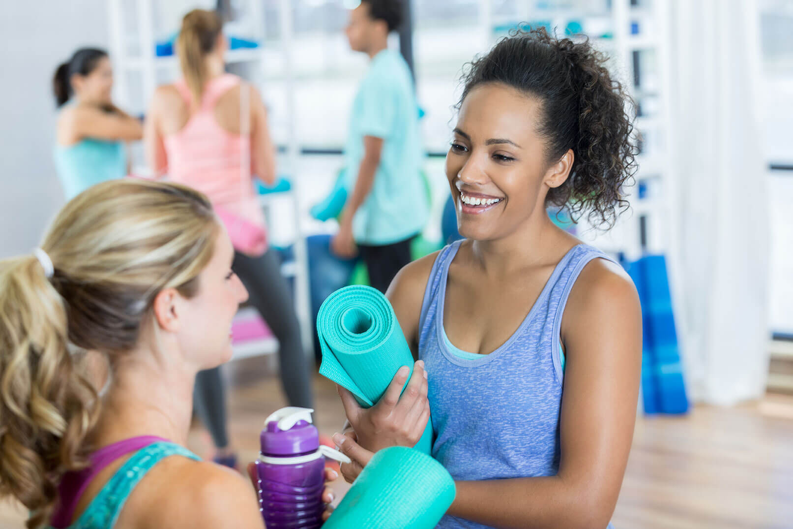 woman with yoga mat talking to friend
